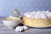 Tasty homemade meringue cake on wooden table, on blue background — Stock Photo