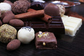 Bars of chocolate and round sweet truffles on the dark wooden smooth background — Stock Photo
