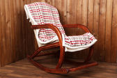 Rocking chair covered with plaid on wooden wall background — Stock Photo