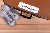Travel suitcase with inscription travel insurance on wooden background  — Stock Photo