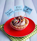 Delicious cake with calories count labels on color plate with napkin, on color wooden table background — Stock Photo