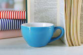 Color cup of tea with books on table, on light blurred background — Foto Stock