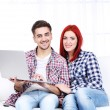 Young couple sitting in sofa with notebook in room — Stock Photo #61490539