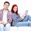 Young couple sitting in sofa with notebook in room — Stock Photo #61490553