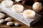 Composition of spa treatment, candles in bowl with water on wooden background — Stock Photo