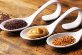 Mustard seeds, powder and sauce in spoons on wooden background — Stock Photo