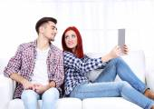 Young couple sitting in sofa with notebook in room — Foto de Stock