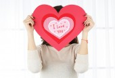 Girl holding Valentine card on bright background — Stock Photo