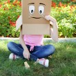 Woman with cardboard box on her head with sad face and ice cream on green grass, outdoors — Stock Photo #61518037