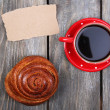 Composition of coffee, fresh bun and paper card on wooden background — Stock Photo #61518099