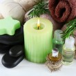 Branches of rosemary and sea salt, towels, candle and bottle with massage oil on color wooden background. Rosemary spa concept — Stock Photo #61518417