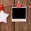 Blank photo frame and Christmas decor on rope, on wooden background — Stock Photo #61518759