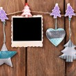 Blank photo frame and Christmas decor on rope, on wooden background — Stock Photo #61518767