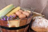 Wooden basket with flowers, maize and eggs on sacking background — Stock Photo