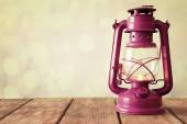 Oil lamp on wooden surface and blurred background — Stockfoto