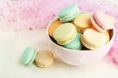 Assortment of gentle colorful macaroons in colorful bowl on color wooden table, on light background — Stock Photo