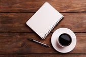 Cup of coffee on saucer with notebook and pen on wooden table background — Stock Photo