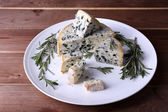Blue cheese with sprigs of rosemary on plate and wooden table background — Stock Photo