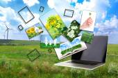 Laptop and images of nature on field and sky background — Stock Photo