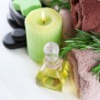 Branches of rosemary and sea salt, towels, candle and bottle with massage oil on color wooden background. Rosemary spa concept — Stock Photo #61608461
