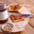 Toast bread spread with jam on piece of paper with knife near jar on wooden table background — Stock Photo #61608783