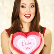 Smiling girl holding Valentines card with greetings on lights background — Stock Photo #61609369