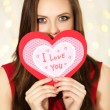 Smiling girl holding Valentines card with greetings on lights background — Stock Photo #61609371
