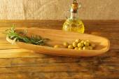 Green olives and branch in oblong bowl with oil can on rustic wooden table, on burlap background — Stock Photo