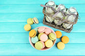Assortment of gentle colorful macaroons in colorful bowl milk bottles on color wooden background — Stock Photo
