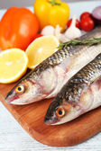Fresh raw fish and food ingredients on table — Stock Photo