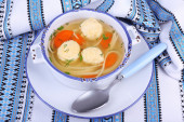 Soup with meatballs and noodles in bowl, on napkin, on wooden background — Stock Photo