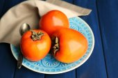 Ripe sweet persimmons, on wooden table — Stockfoto