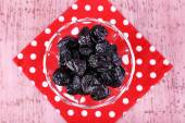 Prunes in glass bowl on polka-dot napkin on color wooden background — Stock Photo
