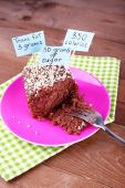 Chocolate cake with calories count labels and fork on color plate and napkin, on wooden table background — Stock Photo