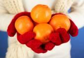 Fresh ripe mandarins in female hands, close-up, on blue background — Stock Photo