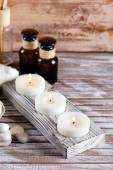 Composition of candles and bottles with massage oil on wooden background — Stock Photo
