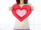 Girl holding Valentine card on bright background — Stockfoto