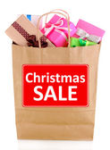Presents in paper bag with Christmas Sale text on it isolated on white — Stockfoto