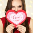 Smiling girl holding Valentines card with greetings on lights background — Stock Photo #61695139