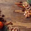 Orange with cookies, spices, slices of dried lemon and sprigs of Christmas tree on rustic wooden background — Stock Photo #61694419