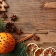 Orange with cookies, spices, slices of dried lemon and sprigs of Christmas tree on rustic wooden background — Stock Photo #61694461