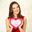 Smiling girl holding Valentines card with greetings on lights background — Stock Photo #61695097