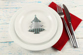 Holiday table setting with Christmas decoration on color wooden background — Stock Photo
