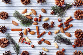 Sprigs of Christmas tree with bumps,  spices and nuts on color wooden background — Stock Photo