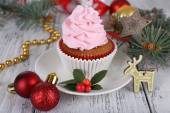 Cup-cake with cream on saucer with Christmas decoration on wooden table background — Stock Photo