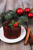 Delicious chocolate cake on saucer with holly and berry on Christmas decoration and wooden background — Stok fotoğraf