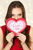 Smiling girl holding Valentines card with greetings on lights background — Stock Photo