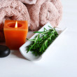 Branches of rosemary  towels, candle, spa stones on color wooden background. Rosemary spa concept — Stock Photo #61735591