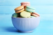 Assortment of gentle colorful macaroons in colorful bowl on color wooden background — Stock Photo