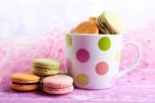 Assortment of gentle colorful macaroons in colorful mug on color wooden table, on light background — Stock Photo